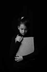Black and white photo of girl looking down, clutching book to her chest