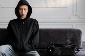 Teenage boy in black hoodie sitting on couch looking sad