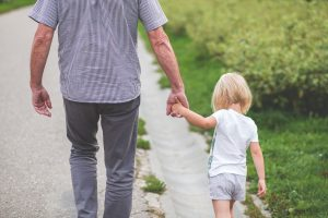 Dad holding child's hand as they are walking