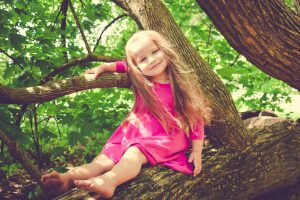 Happy girl sitting in tree, waring a pink dress
