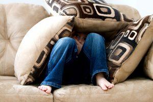 Little boy hiding under pillows
