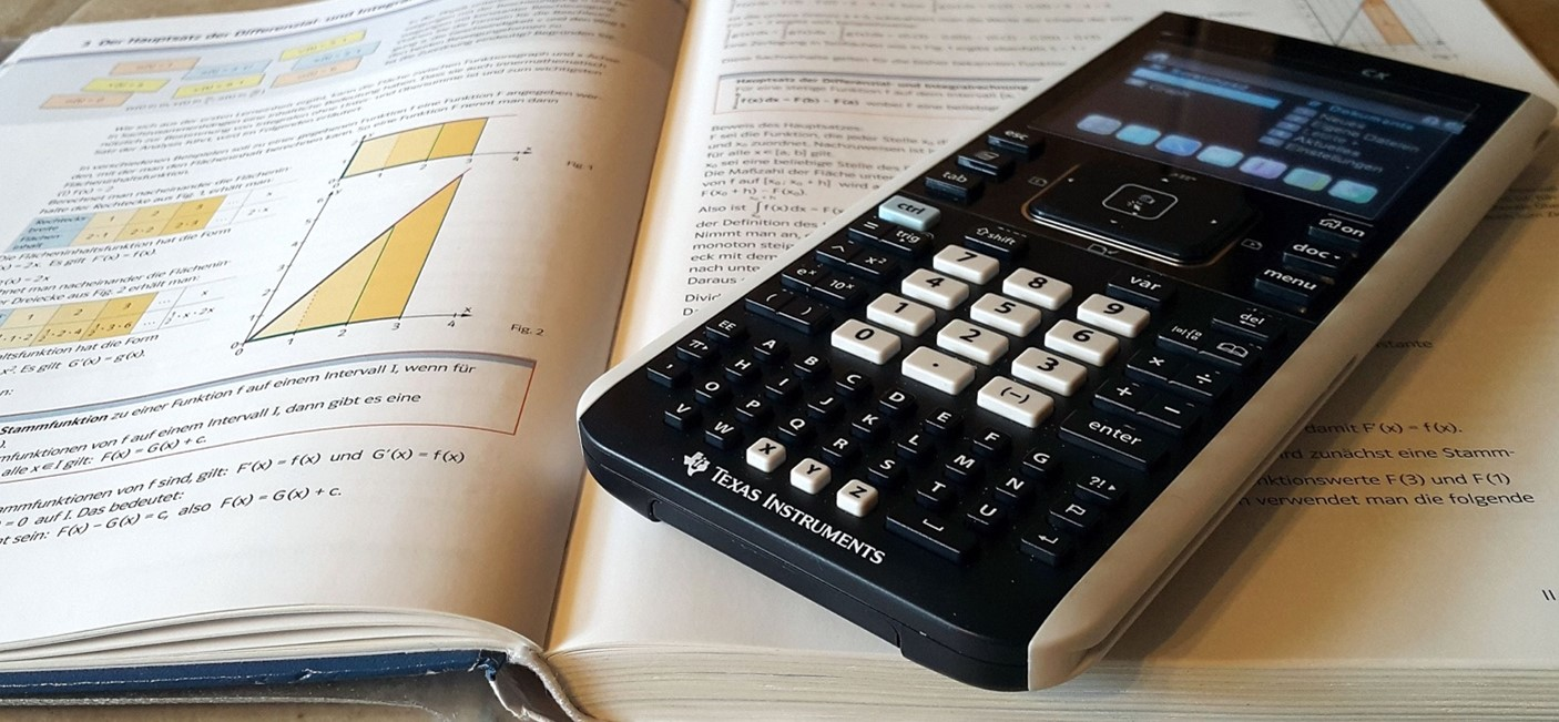 Calculator laying on open textbook