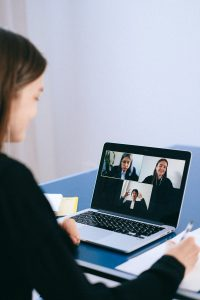 Woman on laptop videoconfrencing with others