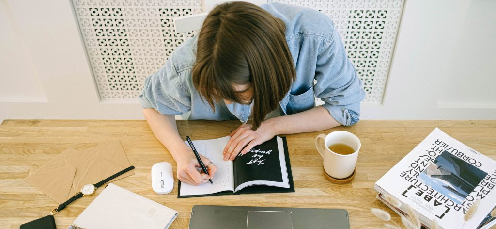 Woman writing notes in notebook in front of laptop