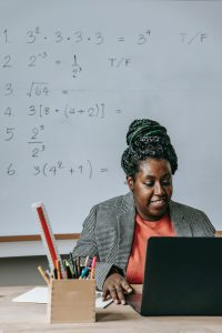 Black woman sitting at desk with laoptop with whiteboard of equations behind her