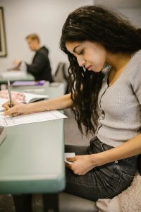 Woman cheating at exam with paper under desk