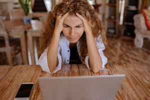 Woman looking at laptop, with hands on head, looking stressed
