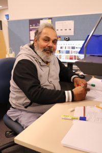 Middle aged aboriginal man sitting at desk